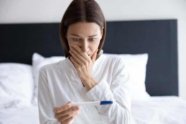 Γυναίκα κοιτά τεστ εγκυμοσύνης στο σπίτι