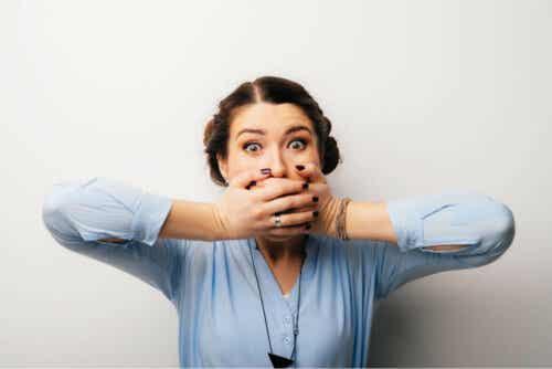 Γυναίκα με τα δύο χέρια μπροστά στο στόμα της