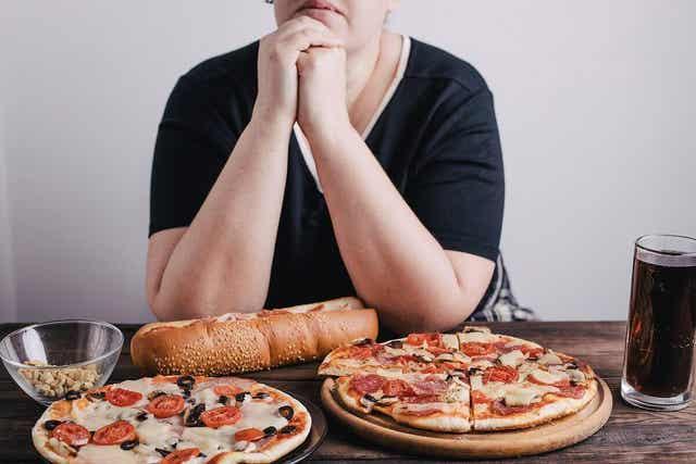 Γυναίκα σε τραπέζι με ανθυγιεινά φαγητά