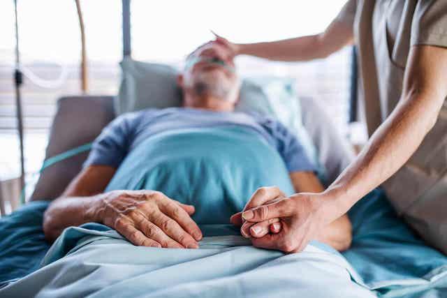 Άτομο κρατά το χέρι ξαπλωμένου ασθενή