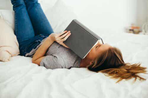 Γυναίκα διαβάζει ξαπλωμένη σε κρεβάτι