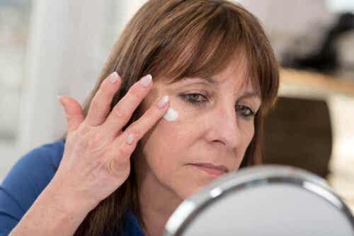 Γυναίκα εφαρμόζει λοσιόν στο πρόσωπό της- ετικέτες των προϊόντων περιποίησης