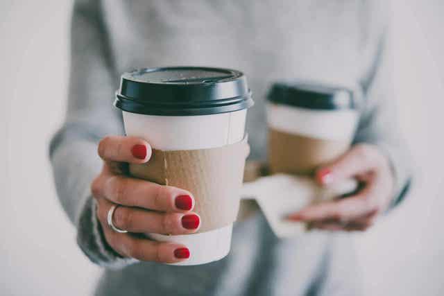 Γυναίκα κρατά δύο ποτήρια με καφέ