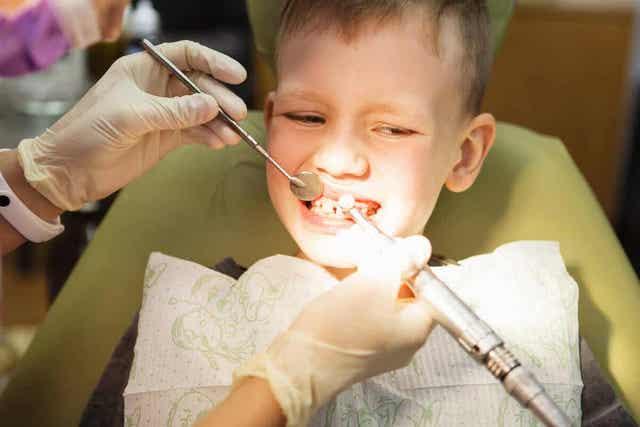 Οδοντίατρος ελέγχει τα δόντια παιδιού