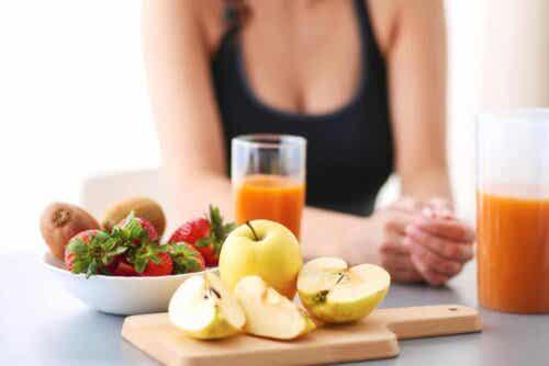 Γυναίκα με φρούτα και χυμούς μπροστά της